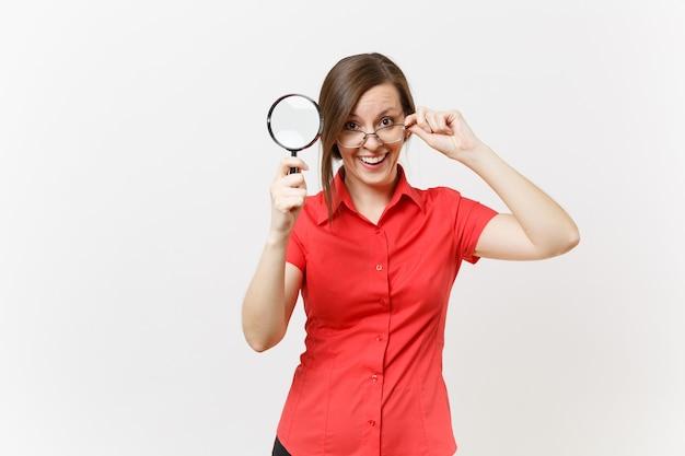 흰색 배경에 고립 된 돋보기를 통해 찾고 빨간 셔츠 안경을 들고 재미 꽤 젊은 비즈니스 교사 여자의 초상화. 고등학교 대학 개념의 교육 또는 교육