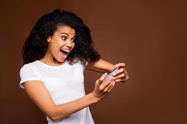 ファンキーでクレイジーなアフロアメリカンの女の子の肖像画は、スマートフォンを使用してビデオゲームをプレイし、スタイリッシュな服を着て叫び声を上げたいです。