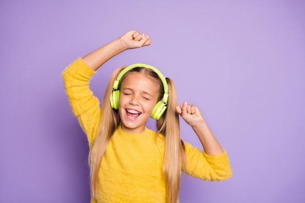 Портрет веселого сумасшедшего ребенка с хвостиками, слушать музыку, перерыв, пауза, использовать гарнитуру, петь песню, танцевать на вечеринке, носить модный джемпер, изолированный на стене фиолетового цвета