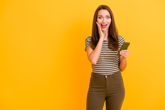 ファンキーな女の子の肖像ソーシャルメディア中毒ユーザー携帯電話を保持信じられないほどの販売ニュースを読む感動悲鳴すごいomgタッチ手顔着用格好良い服孤立した明るい色の壁