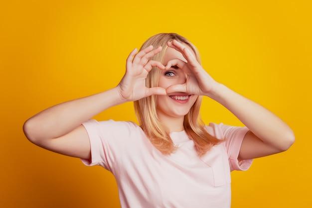 웃긴 사랑스러운 애정 어린 소녀의 초상화는 노란색 배경에 하트 제스처 커버 눈을 보여줍니다.