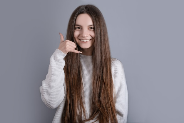 面白い愛らしい若い女性の女性の女の子がセーターを着ている肖像画は、私たちに電話をかけて、電話をかけて、彼女の背中を孤立した灰色の背景に電話するように求めています。
