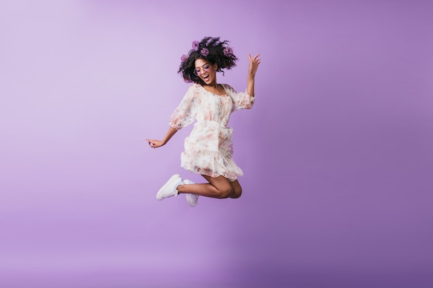 흰색 복장 점프에 재미있는 아프리카 여자의 초상화. 긍정적 인 감정을 표현하는 blithesome 갈색 머리 젊은 여자.