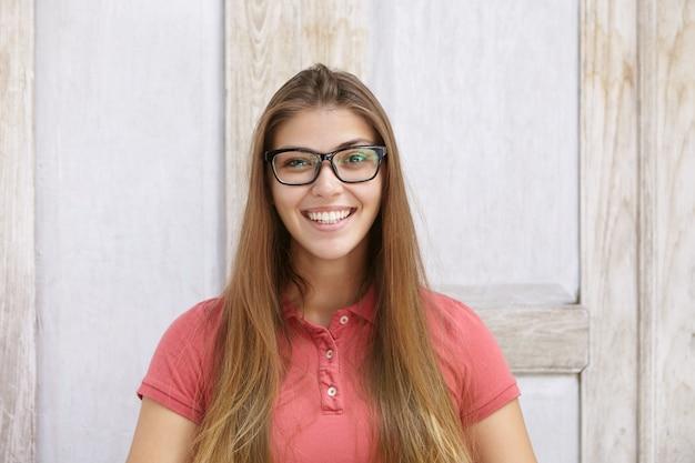 長方形のメガネとポロシャツを着て面白いと陽気な若い白人女性の肖像画を探して、彼女の白い歯を見せて喜んで笑顔