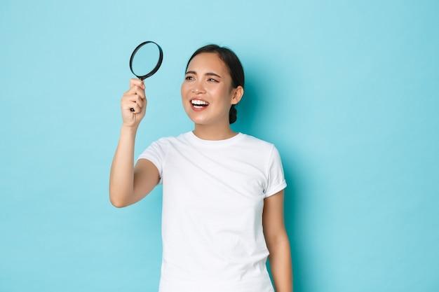 白いtシャツで面白いとかわいいアジアの女性の肖像画、何かを探して、虫眼鏡を通して小さな文字を読んで、困惑した、立っている水色の壁を目を細めて