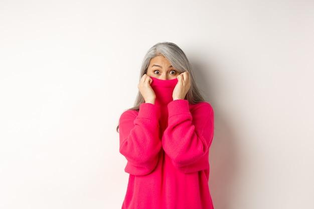 セーターの襟に顔を隠し、愚かなカメラをのぞき、白い背景の上に立っている面白いアジアの祖母の肖像画