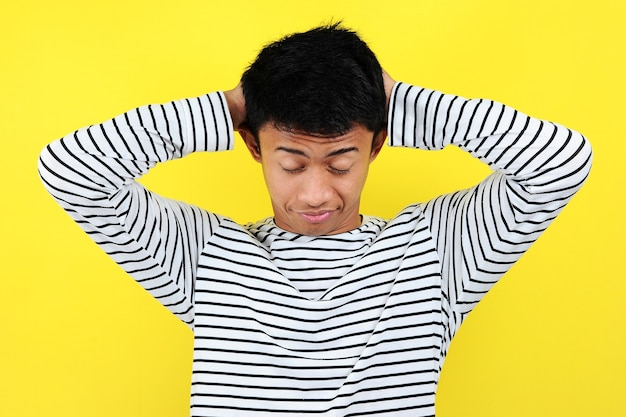 졸린 몸짓을 보여주는 재미있는 아시아 남자의 초상화. 노란색 배경에 고립되어 힘든 일에 지친 느낌