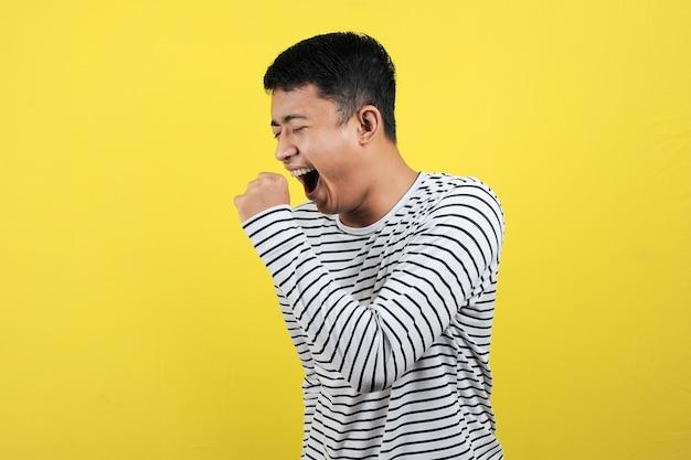 開いた口を覆い、眠そうなジェスチャーを示すあくびをしている面白いアジア人の肖像画。黄色の背景で隔離、ハードワークに疲れている感じ