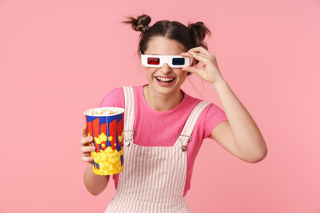ポップコーンと紙コップを保持し、ピンクの壁に孤立して笑っている3dメガネで面白い美しい少女の肖像画