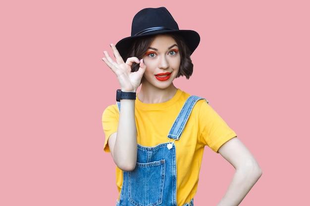 노란색 티셔츠와 파란색 데님 바지를 입은 우스꽝스러운 젊은 여성의 초상화. 분홍색 배경에 격리된 실내 스튜디오 샷입니다.