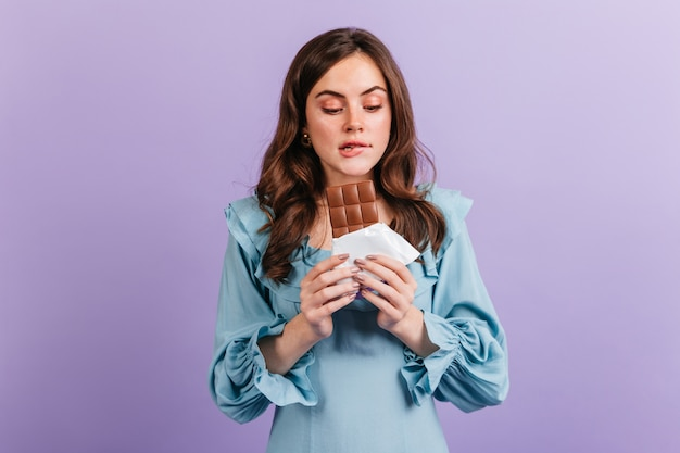 맛있는 점심을 기대 하 고 그녀의 입술을 물고 재미있는 갈색 머리 여자의 초상화. 파란 드레스에 소녀는 맛있는 초콜릿을 살펴 봅니다.