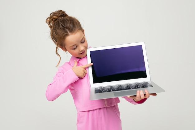 Портрет забавного очаровательного ребенка в розовом костюме, показывающего экран ноутбука