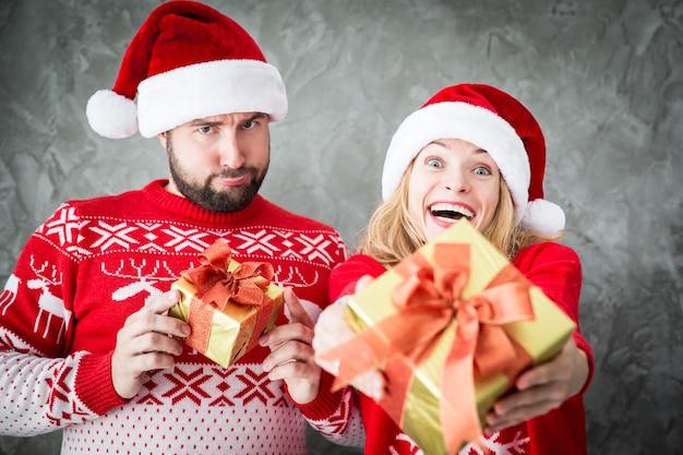 クリスマスプレゼントと面白いカップルの肖像画。一緒に楽しんでいる男性と女性