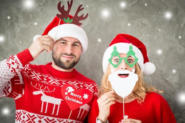 クリスマスの紙の小道具と面白いカップルの肖像画。一緒に楽しんでいる男性と女性