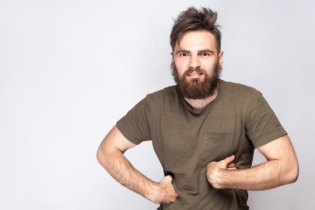 밝은 회색 배경에 짙은 녹색 티셔츠를 입은 재미있는 수염 난 남자의 초상화. 스튜디오 촬영. .