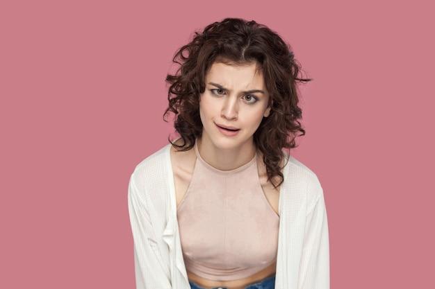 곱슬머리를 한 캐주얼한 스타일로 서서 눈을 마주보고 있는 재미있는 미친 귀여운 브루네트 젊은 여성의 초상화. 표현과 감정. 분홍색 배경에 격리된 실내 스튜디오 샷입니다.