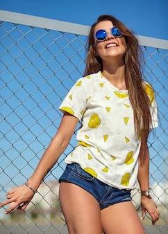 철 격자와 푸른 하늘 뒤에 거리에서 포즈 밝은 힙 스터 여름 캐주얼 옷에 재미 미친 매력적인 세련된 웃는 아름다운 젊은 여성 모델의 초상화