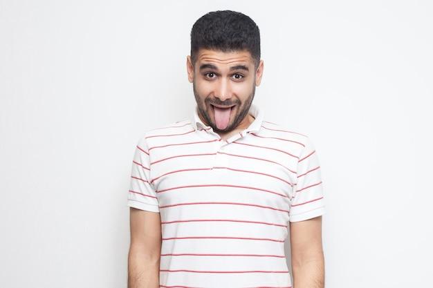 Портрет забавного сумасшедшего красивого бородатого молодого человека в полосатой футболке, стоящего, высунувшего язык и смотрящего в камеру с забавным лицом. крытая студия выстрел, изолированные на белом фоне.