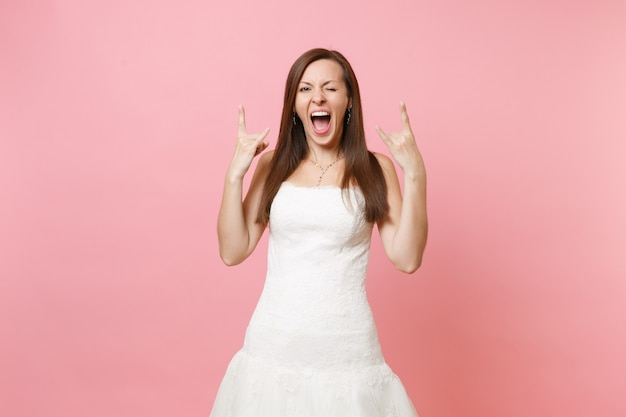Портрет смешной сумасшедшей женщины в белом платье стоя, моргая и показывая знак рок-н-ролла