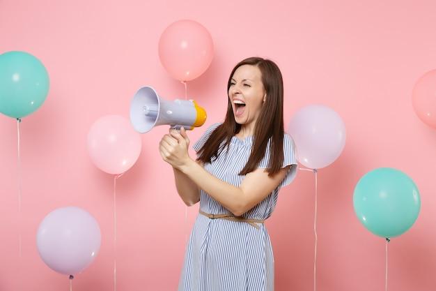 Портрет смешной сумасшедшей молодой красивой женщины в синем платье, держащей мегафон, кричащий на пастельно-розовом фоне с красочными воздушными шарами. праздник дня рождения, концепция искренних эмоций людей.
