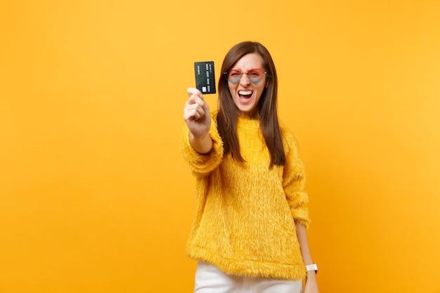 明るい黄色の背景で隔離のカメラでクレジットカードを示す毛皮のセーターとハートの眼鏡で面白い狂気の若い女性の肖像画。人々の誠実な感情のライフスタイルの概念。広告エリア。