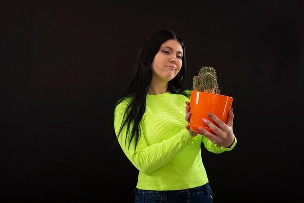 Портрет молодой женщины с забавным лицом, держащей кактус в горшке, изолированные