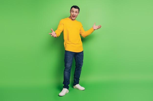 面白い軽薄な男の肖像画は、緑の背景に楽しい陽気な顔をしています