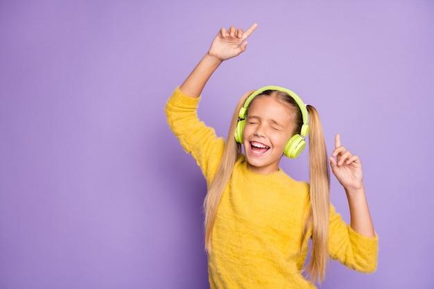 Портрет забавного фанк-сумасшедшего ребенка, перерыв, пауза, веселье, пение песни, использование зеленой гарнитуры, прослушивание музыки, танцевальная одежда, стильный пуловер, изолированный на стене фиолетового цвета