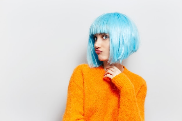 흰 벽에 주황색 스웨터에 파란 머리를 가진 재미있는 여자의 초상화.