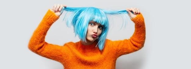 Портрет смешной девушки с голубым париком и оранжевым свитером, на светлой спине.