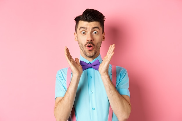 面白い男の肖像画は、カメラを驚かせて見つめ、素晴らしいオファーをチェックし、ピンクの背景に上品な蝶ネクタイで立って、すごいと言います