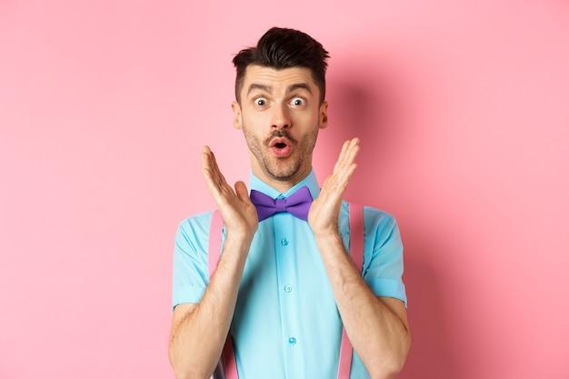 Портрет забавного парня говорит «вау», изумленно смотрит в камеру, рассматривает потрясающее предложение, стоит в классном галстуке-бабочке на розовом.