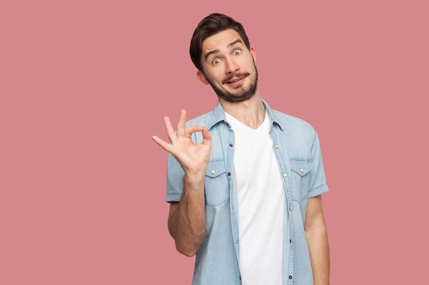 파란색 캐주얼 스타일 셔츠를 입은 웃긴 잘생긴 수염난 청년의 초상화는 ok 사인과 함께 서 있고 재미있는 얼굴로 카메라를 보고 있습니다. 실내 스튜디오 촬영, 분홍색 배경에 격리.
