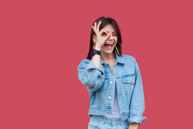 데님 캐주얼 스타일의 화장을 한 재미있는 행복한 아름다운 브루네트 젊은 여성의 초상화는 그녀의 눈에 확인 표시가 있고 카메라를 보고 있습니다. 실내 스튜디오 촬영, 빨간색 배경에 고립.