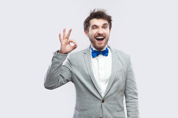 회색 양복에 파란색 나비 넥타이를 매고 ok 사인을 하고 카메라를 쳐다보며 윙크를 하는 웃긴 행복한 수염 난 남자의 초상화. 밝은 회색 배경에 격리된 실내 스튜디오 촬영.