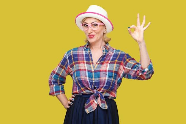 모자와 안경을 쓴 캐주얼한 스타일의 재미있고 현대적인 귀엽고 세련된 성숙한 여성의 초상화는 ok 사인과 함께 서서 카메라를 바라보며 웃고 있습니다. 노란색 배경에 격리된 실내 스튜디오 샷입니다.