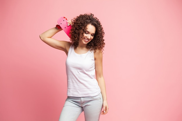 ピンクの上にピンクのロングボードを持つ面白いヒップスターの女の子の肖像画。