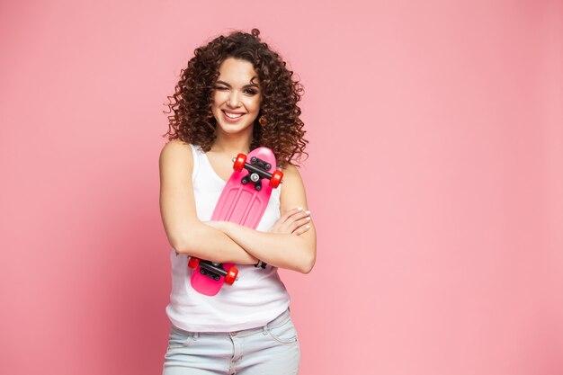 핑크 위에 핑크 longboard와 재미있는 hipster 여자의 초상화.
