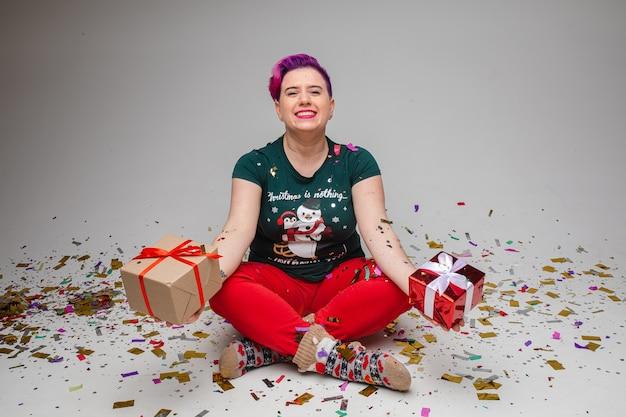 紙吹雪で覆われた床に座っている間、手に2つの包まれたプレゼントを示すクリスマスのパジャマと靴下の紫色の髪を持つ面白い陽気な女性の肖像画