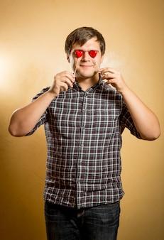 Портрет забавного человека, держащего красные сердца перед глазами