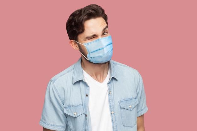 青いカジュアルなスタイルのシャツに立って、ウインクして、変な顔と笑顔でカメラを見ているサージカルマスクを持つ変な男の肖像画。ピンクの背景に分離された屋内スタジオショット。