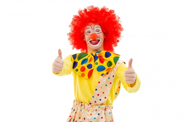 Портрет смешного шаловливого клоуна в красном парике показывая одобренный знак.