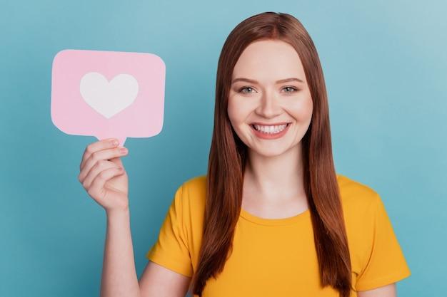 재미있는 긍정적인 여성의 초상화는 파란색 배경에 심장 알림 카드를 들고 있습니다.
