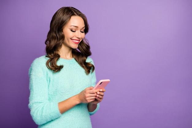 Портрет забавной симпатичной леди держать телефон в руках писать новый творческий пост блог влиятельного лица носить пастельный случайный пушистый пушистый свитер.