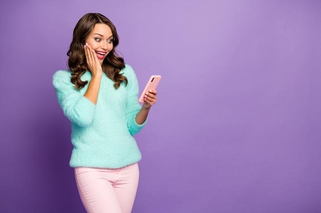 Портрет забавной симпатичной дамы модель держать телефон в руках блогер блогер читать новые комментарии носить повседневный пушистый пушистый свитер пастельно-розовые штаны.