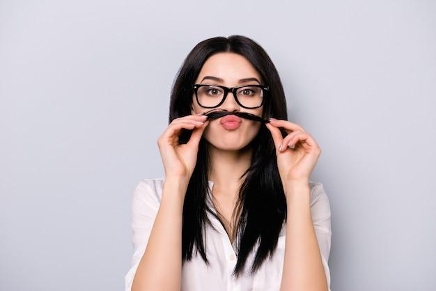 Портрет забавной симпатичной молодой брюнетки в очках, держащей волосы над губами, как у усов, стоя на сером пространстве