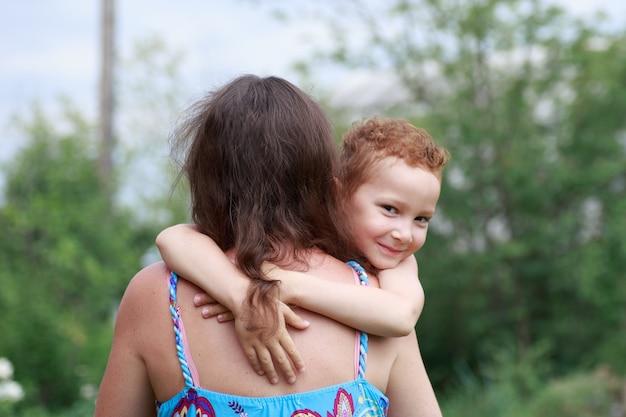 Портрет забавного рыжего мальчика с веснушками обнимает маму вокруг шеи.