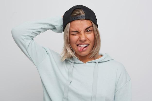 Портрет забавной расслабленной блондинки с подтяжками на зубах в черной кепке и толстовке с капюшоном показывает язык, подмигивает и веселится, изолированно от белой стены