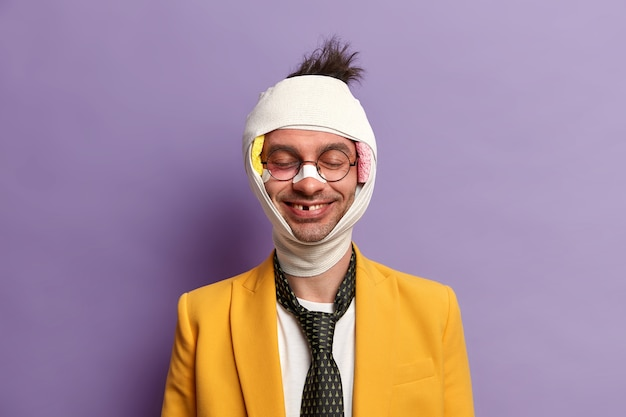 面白い笑顔の男の肖像は、深刻な外傷の後に歯が欠けている、目を閉じて立っている、傷ついた皮膚、包帯を巻いた頭、自転車に乗っている間に落ちた、回復期間があり、紫色の壁に隔離されています