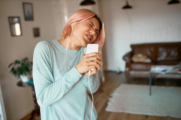 Портрет забавной стильной молодой женщины с розовыми волосами, позирующей в уютном интерьере квартиры в наушниках